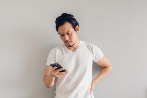 Un homme sérieux aux cheveux longs en t-shirt décontracté blanc utilise un smartphone