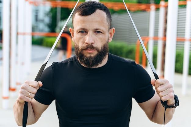 Un homme sérieux avec une barbe est engagé en plein air. l'homme est engagé dans un ajustement croisé, effectue des exercices avec persistance, regarde la caméra