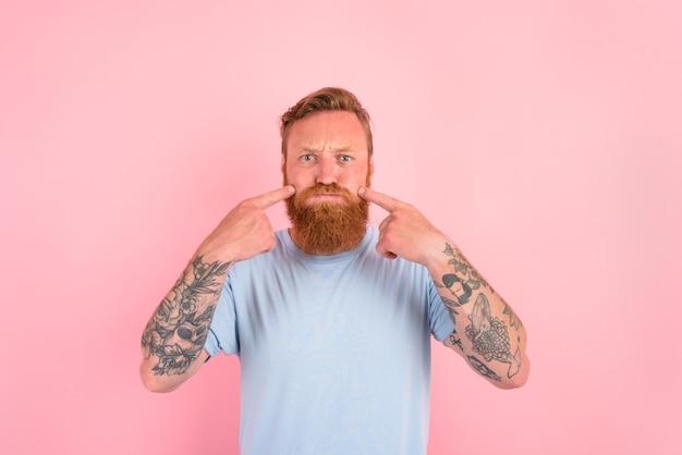 Homme sérieux avec barbe et t-shirt bleu clair