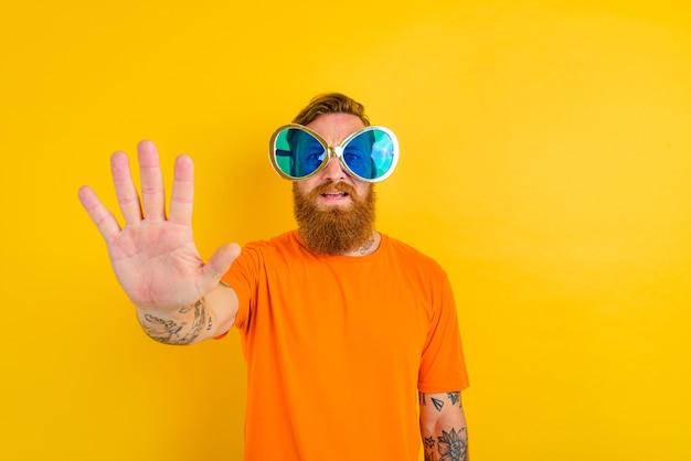 Homme sérieux avec barbe, tatouage et grandes lunettes de soleil