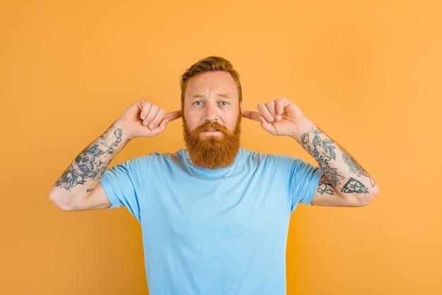L'homme sérieux avec la barbe et le tatouage ne veut pas entendre