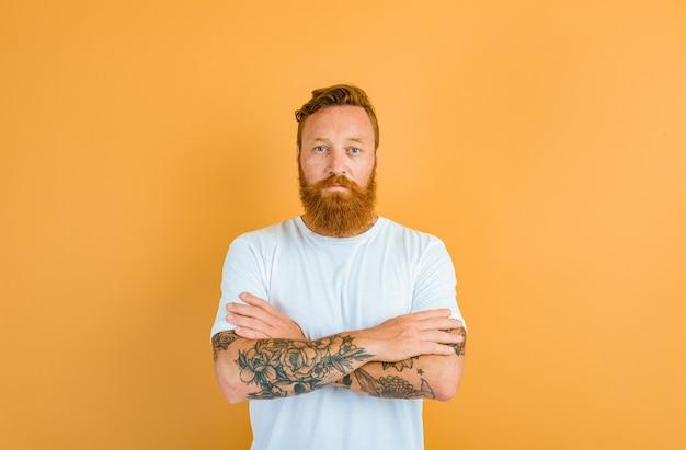 Homme sérieux avec barbe, tatouage et t-shirt blanc