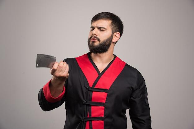 Homme sérieux avec barbe tenant un couteau bien aiguisé.
