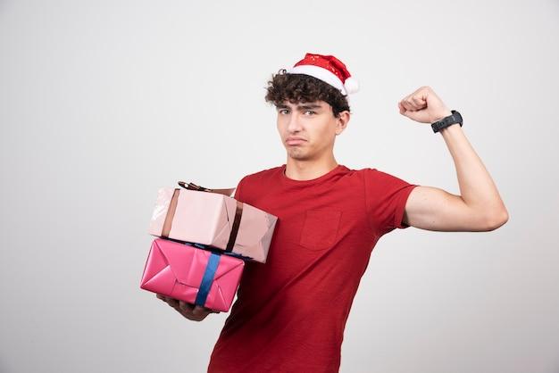 Homme sérieux en bonnet de noel tenant des cadeaux