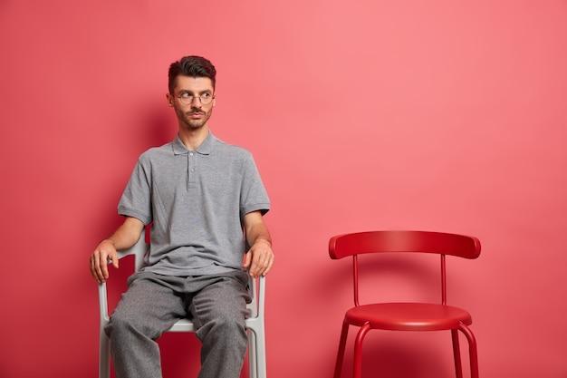Homme sérieux avec chaume vêtu de vêtements décontractés pose sur une chaise regarde pensivement quelque part
