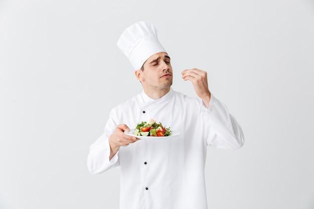 Homme sérieux chef cuisinier en uniforme montrant salade verte fraîche sur une assiette isolée sur mur blanc