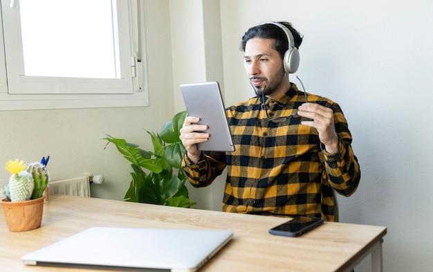 Homme sérieux en chemise à carreaux jaune assis dans un bureau avec une tablette dans les mains et des écouteurs