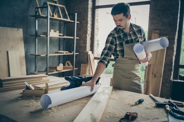 Homme sérieux concentré concentré tenant des plans roulés avec des dépôts sur toile placés avec de nombreux outils