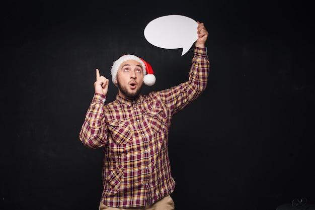 Homme sérieux drôle en bonnet de noël rouge de noël détient un carton blanc vide comme blanc ou maquette avec espace de copie pour le texte. fond noir