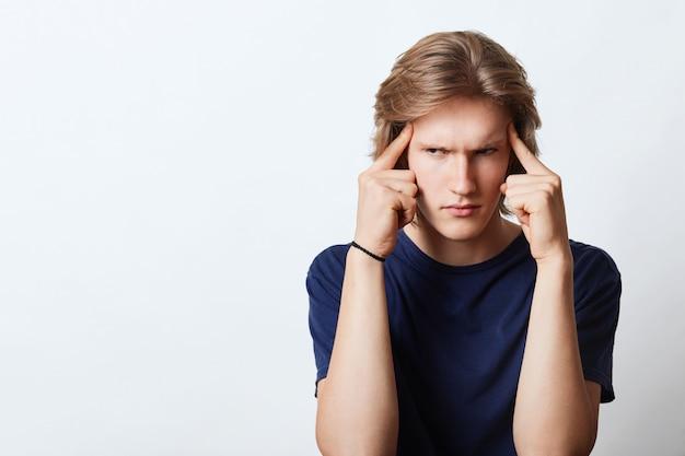 Homme sérieux essayant de se concentrer, gardant les doigts sur la tête, prenant une décision importante avec une expression de colère. jeune homme d'affaires occupé à travailler en essayant de se concentrer sur quelque chose d'important