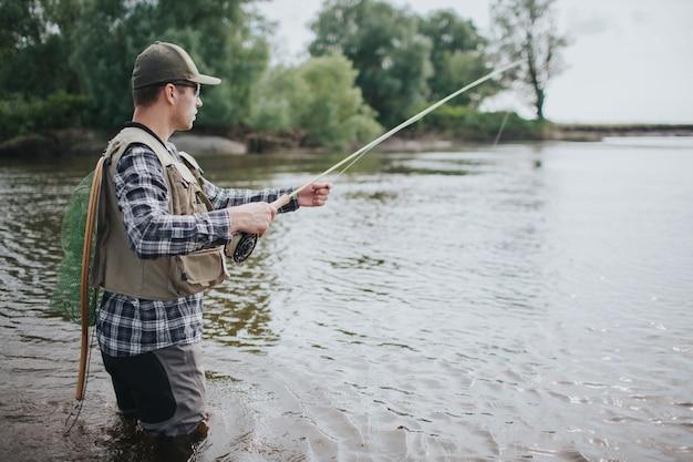 Un homme sérieux est debout dans l'eau et la pêche. il a tourné dans les mains et un filet de pêche dans le dos. guy porte gilet, cuissardes, chemise et casquette.