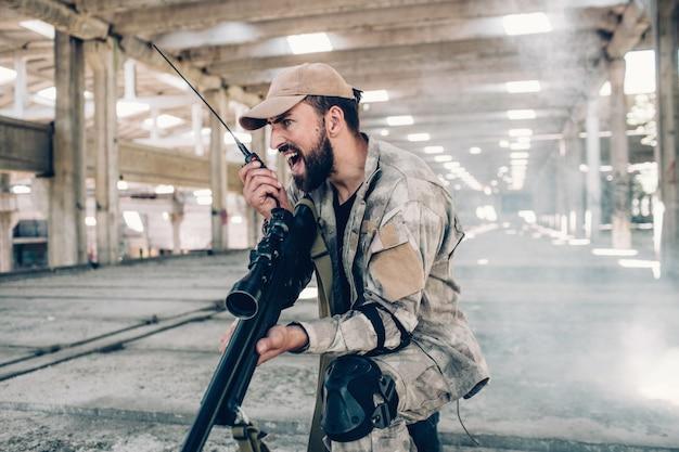 Un homme sérieux est debout dans un hangar et tient un pistolet de paintball dans les mains.