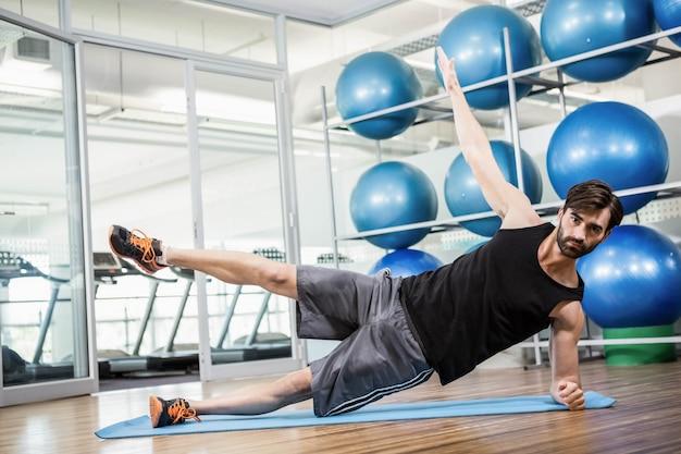 Homme sérieux faisant des exercices sur le tapis dans le studio