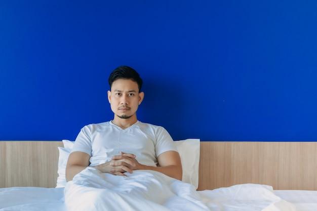 Un homme sérieux et grincheux se réveille sur le lit sur fond d'espace bleu