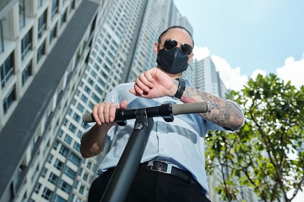 Homme sérieux en lunettes de soleil et masque de protection debout sur un scooter électrique et vérifiant la notification sur smartwatch