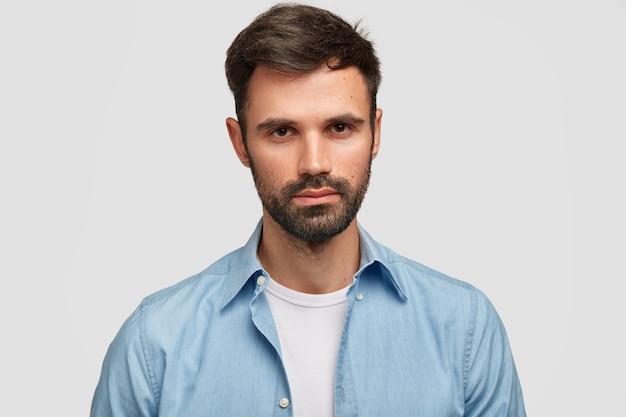 Homme sérieux mal rasé avec une apparence agréable, a les cheveux noirs, des poils, contemple quelque chose d'important, vêtu de vêtements à la mode, isolé sur un mur blanc. homme européen à l'intérieur