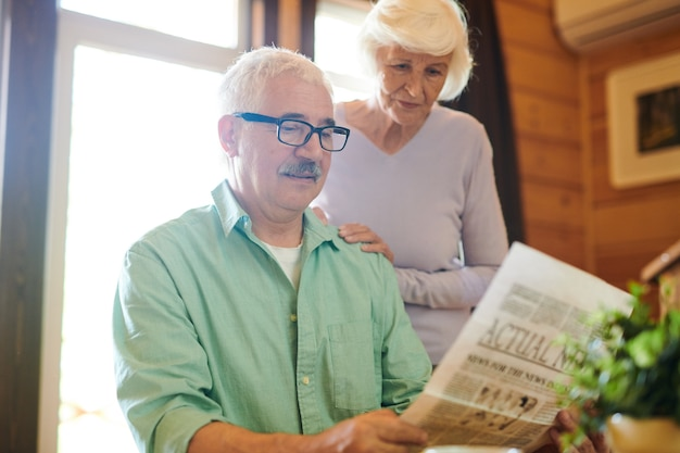 Homme sérieux matue lisant des nouvelles fraîches à sa femme le matin alors qu'il était assis à table dans leur maison de campagne