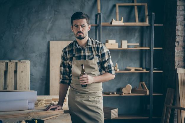 Homme sérieux réfléchi tenant une bouteille de bière avec la main appuyée sur une planche allongée sur la toile en vous regardant tout en buvant