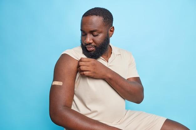Un homme sérieux regarde le bras avec du plâtre s'est fait vacciner pendant la pandémie de coronavirus se trouve à l'intérieur contre le mur bleu