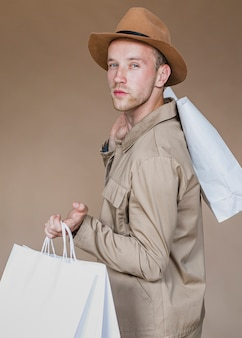 Homme sérieux avec des sacs à provisions à la recherche de la caméra