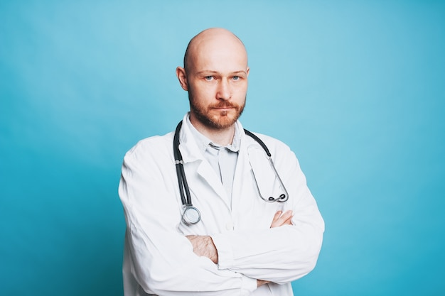 Homme sérieux séduisant docteur barbu chauve regardant la caméra isolé sur fond bleu