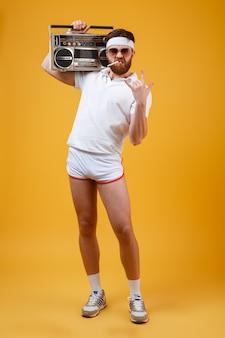 Homme sérieux tenant un magnétophone faire un geste rock.