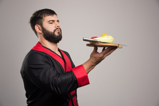 Homme sérieux tenant une planche de bois avec poivron jaune, courgettes et couteau.