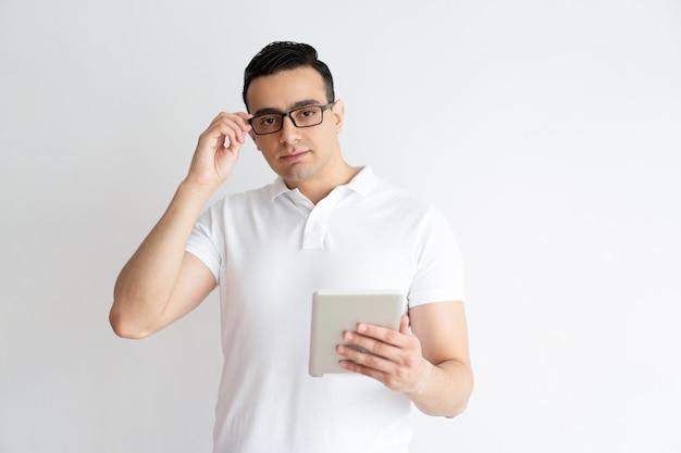 Homme sérieux tenant une tablette et ajustant des lunettes.