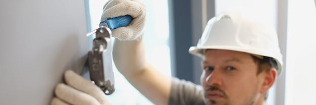 Un homme serre un morceau de garnitures en métal avec une réparation de tournevis de la porte d'armoire dedans
