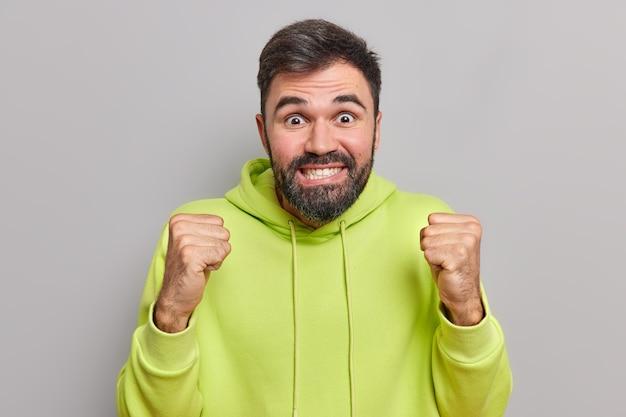 L'homme serre les poings racines pour l'équipe de football préférée anticipe les résultats ne peut pas attendre quelque chose vêtu de sweat-shirt pose sur gris