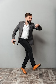 Homme serré sur toute la longueur avec du café à emporter en regardant la montre en retard et en cours d'exécution le long de gris