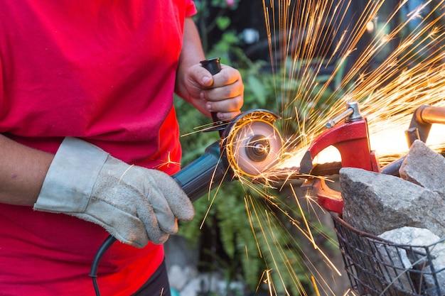 Homme serrurier utilisant une scie pour couper un morceau de fer à l'extérieur.