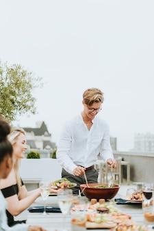 Homme servant la salade de ses amis lors d'une fête sur le toit