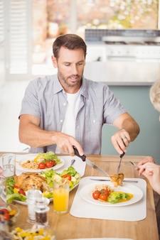 Homme servant de la viande dans l'assiette tout en déjeunant