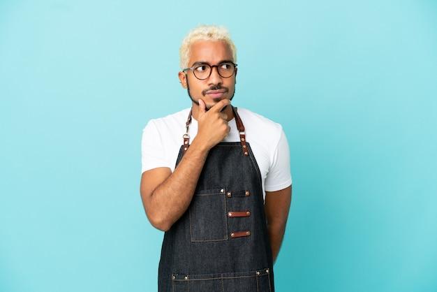 Homme de serveur colombien de restaurant isolé sur fond bleu ayant des doutes et avec une expression de visage confuse