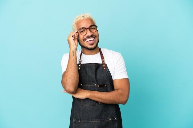 Homme de serveur colombien de restaurant d'isolement sur le fond bleu avec des verres et heureux