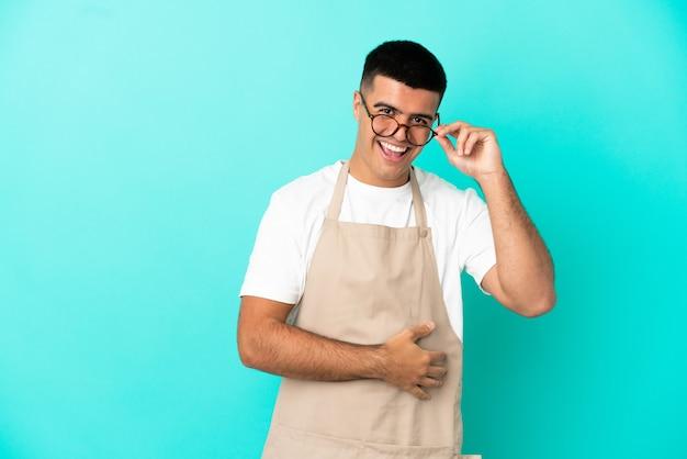 Homme de serveur de restaurant sur fond bleu isolé avec des lunettes et heureux