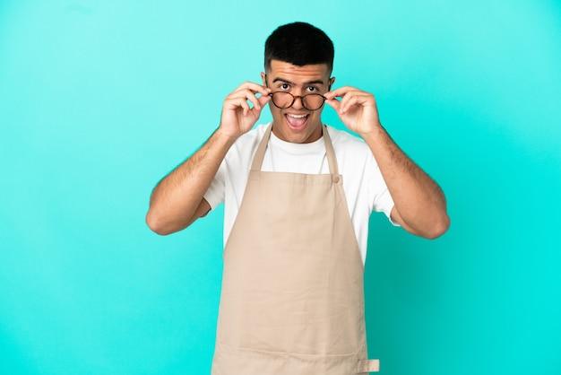 Homme de serveur de restaurant sur fond bleu isolé avec des lunettes et surpris
