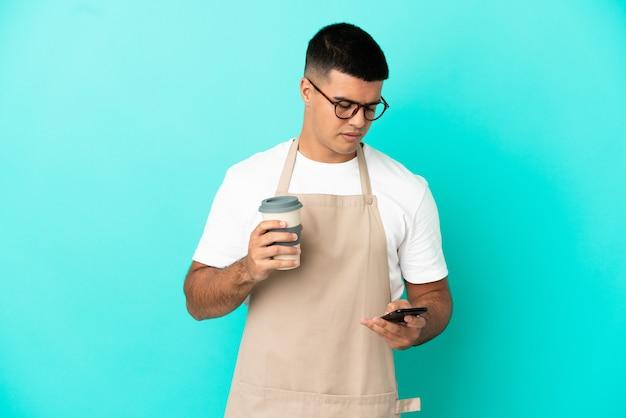 Homme de serveur de restaurant sur un mur bleu isolé tenant du café à emporter et un mobile