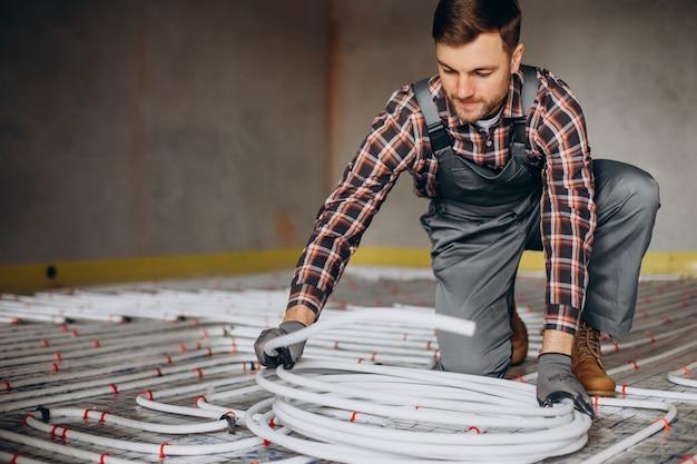 Homme de service instellant le système de chauffage de la maison sous le plancher