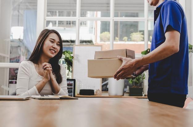 Homme de service de livraison à domicile intelligent en uniforme bleu et jolie jeune cliente asiatique