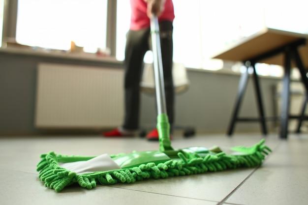 Homme de service de nettoyage essuyant le sol dans la chambre