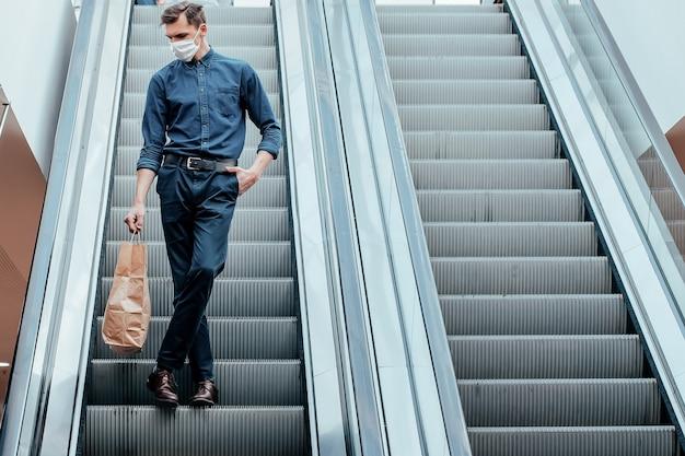 Homme seul dans un masque de protection debout sur les marches de l'escalator. photo avec un espace de copie