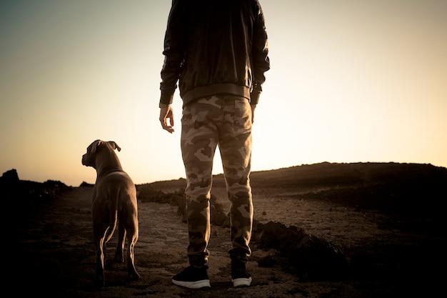 Homme seul et meilleur ami chien marchant ensemble sur un chemin dans une activité de loisirs en plein air dans le désert avec l'océan à la fin
