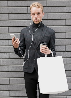 Homme seul avec des sacs à provisions et smartphone