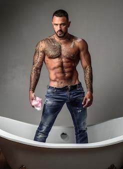 Homme sexy athlétique musclé avec torse nu. homme au corps tatoué. homme brutal confiant et beau. la santé des hommes. beau torse masculin.