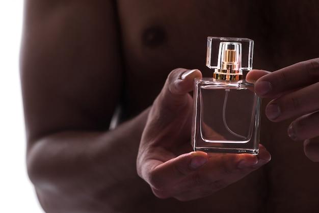 Homme sexy avec une bouteille de parfum