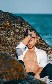 Homme sexy en chemise mouillée sur la plage