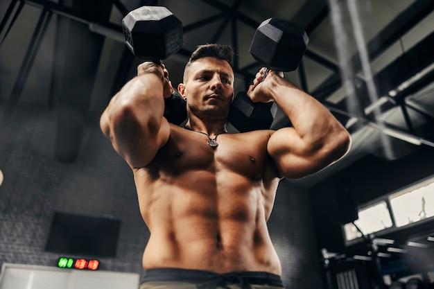 Homme sexy avec un haut du corps nu soulevant des haltères lourds avec les deux mains dans l'atmosphère sombre d'un gymnase