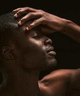 Un homme sexy à la peau sombre fait un geste de visage de paume. guy afro-américain ressent des maux de tête couvrant son visage avec la main posant avec les yeux fermés sur fond noir. photo en gros plan. vue de profil. image tonique
